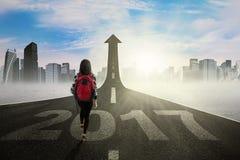 Studente che cammina sulla via con la freccia e 2017 Fotografia Stock Libera da Diritti