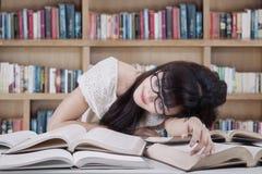 Studente che dorme e che sogna nella biblioteca Fotografie Stock Libere da Diritti