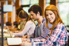 Studente che esamina macchina fotografica mentre studiando con i compagni di classe Immagini Stock Libere da Diritti
