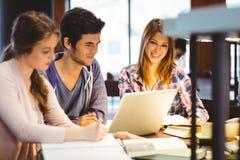 Studente che esamina macchina fotografica mentre studiando con i compagni di classe Immagine Stock