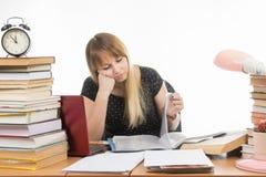 Studente che esamina tristemente le pagine di tornitura in una cartella lo scrittorio fra le pile di libri Immagini Stock