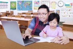 Studente che fa assegnazione di scuola con il suo insegnante Immagini Stock
