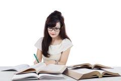 Studente che fa compito della scuola mentre scrivendo sul libro Fotografie Stock Libere da Diritti