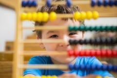 Studente che fa i per la matematica sull'abaco Fotografie Stock Libere da Diritti