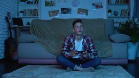 Studente che gioca tardi i video giochi alla notte invece che studia, ragazzo dipendente del gioco stock footage