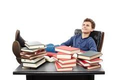 Studente che ha un resto con le gambe sullo scrittorio, fantasticante AMO Fotografie Stock