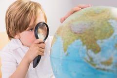 Studente che impara geografia con il globo Fotografie Stock