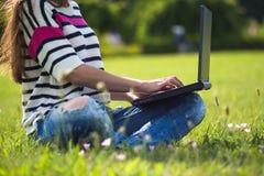 Studente che lavora al computer portatile in parco Fotografie Stock Libere da Diritti