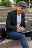 Studente che lavora al suo computer portatile con un berretto irlandese Fotografia Stock