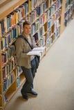Studente che legge un libro che sta nella biblioteca che sorride alla macchina fotografica Fotografia Stock Libera da Diritti
