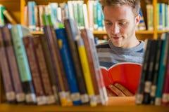 Studente che legge un libro in mezzo degli scaffali per libri nella biblioteca Immagini Stock