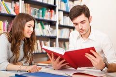 Studente che legge un libro in una biblioteca Immagine Stock