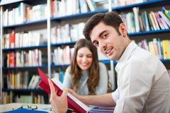 Studente che legge un libro in una biblioteca Fotografie Stock Libere da Diritti