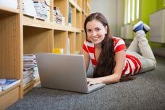 Studente che per mezzo del computer portatile che si trova sul pavimento delle biblioteche Fotografia Stock Libera da Diritti