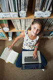 Studente che per mezzo del computer portatile contro lo scaffale per libri sul pavimento delle biblioteche Fotografia Stock Libera da Diritti