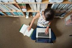 Studente che per mezzo del computer portatile contro lo scaffale per libri sul pavimento delle biblioteche Immagini Stock Libere da Diritti