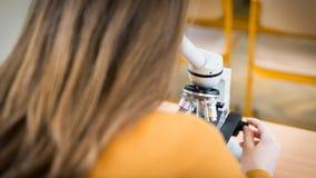Studente che per mezzo del microscopio per esaminare i campioni nella classe di Biologia fotografia stock