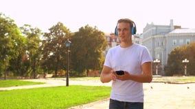 Studente che per mezzo dello smartphone all'aperto archivi video
