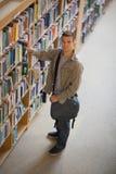 Studente che prende un libro dallo scaffale in biblioteca che sorride alla macchina fotografica Fotografie Stock