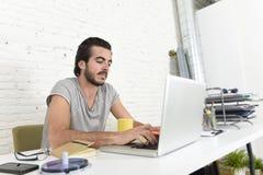 Studente che prepara esame rilassato o uomo d'affari informale di stile dei pantaloni a vita bassa che lavora con il computer por Fotografie Stock