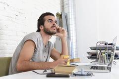 Studente che prepara esame rilassato o uomo d'affari informale di stile dei pantaloni a vita bassa che lavora con il computer por Fotografia Stock