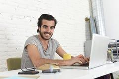 Studente che prepara esame rilassato o uomo d'affari informale di stile dei pantaloni a vita bassa che lavora con il computer por Immagini Stock