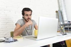 Studente che prepara pensiero dell'esame o uomo d'affari informale di stile dei pantaloni a vita bassa che lavora con il computer Immagini Stock Libere da Diritti