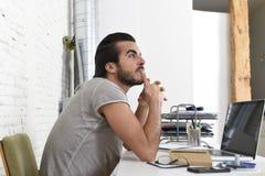 Studente che prepara pensiero dell'esame o uomo d'affari informale di stile dei pantaloni a vita bassa che lavora con il computer Fotografia Stock