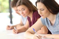 Studente che prova a copiare un esame all'aula Immagine Stock