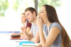 Studente che sbadiglia durante la classe A all'aula Immagini Stock