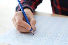 Studente che sceglie le risposte nella forma della prova per passare esame immagine stock libera da diritti