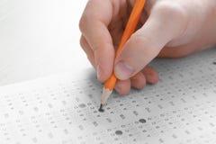 Studente che sceglie le risposte nella forma della prova per passare esame fotografie stock libere da diritti