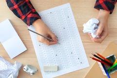 Studente che sceglie le risposte nella forma della prova per passare esame immagini stock libere da diritti