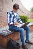 Studente che si siede con il computer portatile facendo uso del telefono cellulare in città universitaria Fotografie Stock Libere da Diritti