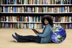 Studente che si siede con il libro ed il globo in biblioteca Immagine Stock
