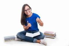 Studente che si siede facendo gesto del vincitore con i libri intorno Immagine Stock