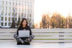 Studente che si siede sul banco che ascolta la musica e che per mezzo del computer portatile che sorride contro il campus univers Fotografie Stock Libere da Diritti