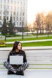 Studente che si siede sul banco che ascolta la musica e che per mezzo del computer portatile contro distogliere lo sguardo del ca Fotografie Stock