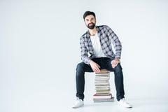 Studente che si siede sul mucchio dei libri su bianco con lo spazio della copia Fotografia Stock Libera da Diritti