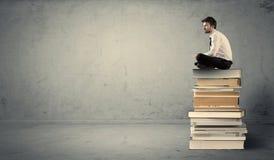 Studente che si siede sulla pila di libri Immagini Stock