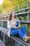 Studente che si siede sulla tribuna di sport e che sorride alla macchina fotografica Fotografia Stock