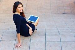 Studente che si siede sulle scale con un computer della compressa Immagini Stock