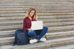 Studente che si siede sulle scale e che lavora con il computer portatile all'aperto Fotografia Stock