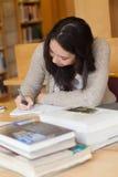 Studente che si siede in una biblioteca ad uno scrittorio e ad una scrittura Fotografie Stock