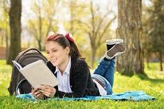 Studente che si trova su un prato che legge un libro Fotografia Stock Libera da Diritti