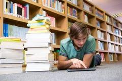 Studente che si trova sul pavimento delle biblioteche Fotografia Stock Libera da Diritti