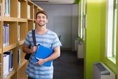 Studente che sorride alla macchina fotografica in biblioteca Immagini Stock Libere da Diritti