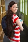 Studente che sorride alla macchina fotografica in biblioteca Fotografia Stock