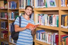 Studente che sorride alla macchina fotografica in biblioteca Immagini Stock