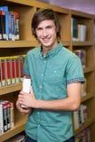 Studente che sorride alla macchina fotografica in biblioteca Fotografie Stock Libere da Diritti